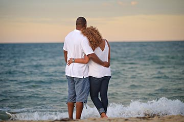 romantic afro-american couple hugging, ocean beach waves splash and sunset in the summer