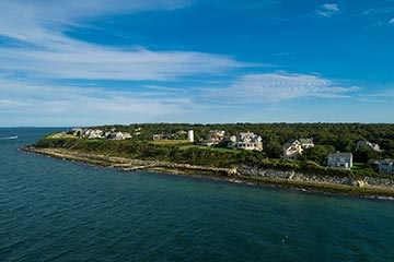 summer aerial photo of ocean view homes and East Chop lighthouse on the hills of Oak Bluffs