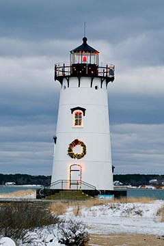 Snow around Edgartown Lighthouse decorated with christmas lights and wreath