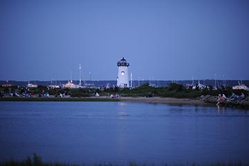 Edgartown harbor yachts and people around lighthouse at dusk Independence Day