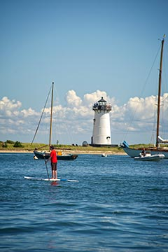 Marthas Vineyard Edgartown lighthouse, boy on paddleboard in the summer