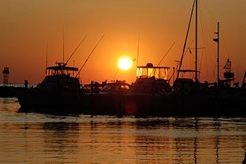 boats shapes on bright orange sunset in Menemsha harbor